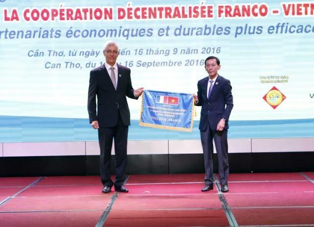 Ông Võ Thành Thống, Chủ tịch UBND TP Cần Thơ trao cờ đăng cai Hội nghị lần thứ 11 dự kiến diễn ra vào năm 2019 cho đại diện thành phố Toulouse (Pháp).