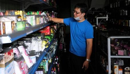 Chủ một tiệm tạp hóa kiểm tra đồ đạc trong cửa hàng.