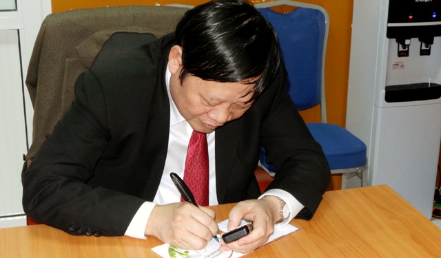 Nhà báo Phạm Huy Hoàn và Thứ trưởng Bộ Y tế Nguyễn Viết Tiến ký tặng đĩa ghi hình đêm trao giải Nhân tài Đất Việt 2015 cho PGS.TS Nguyễn Văn Thạch.