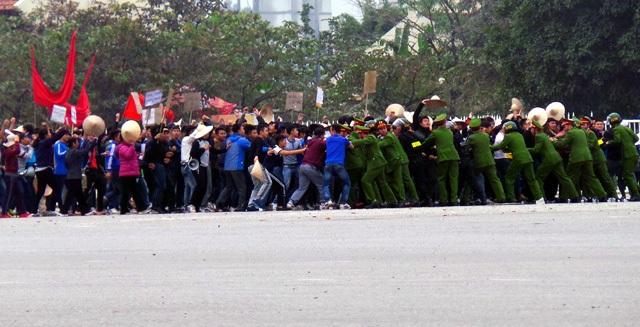 Bị kích động, đám đông tràn lên, gây sức ép với cảnh sát.