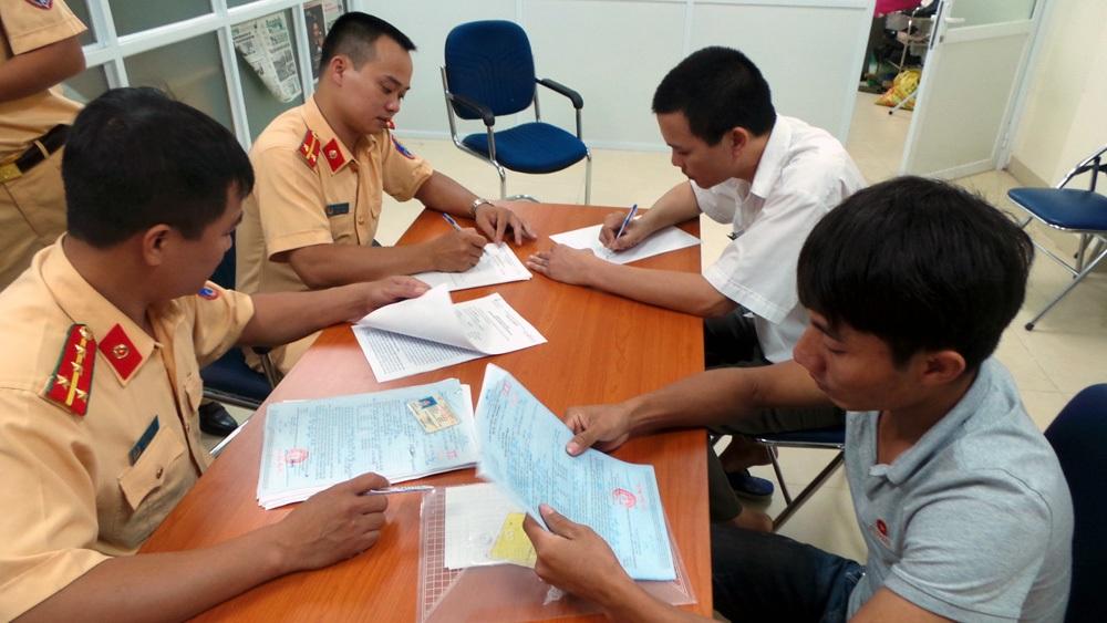Lái xe Lưu Văn Tuấn (áo màu ghi) làm việc với cán bộ Phòng PC67 - CATP Hà Nội.
