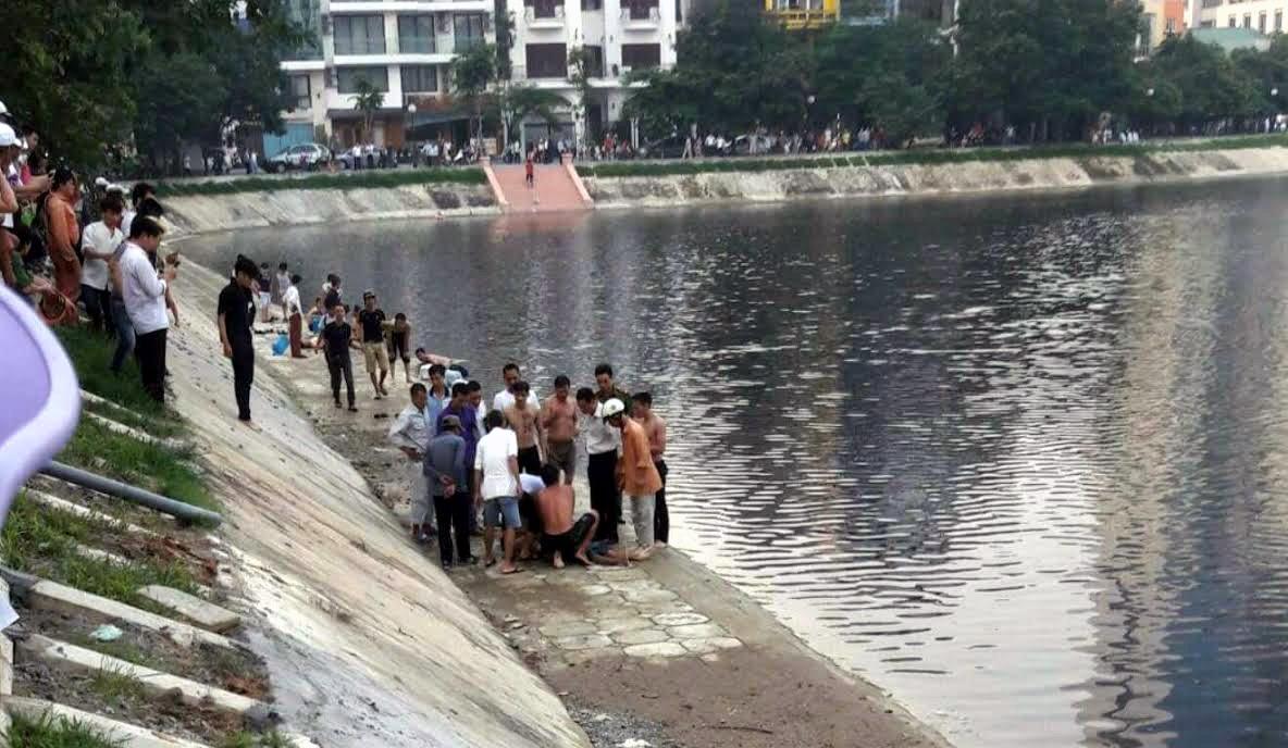 Hai thanh niên được người dân đưa lên bờ.