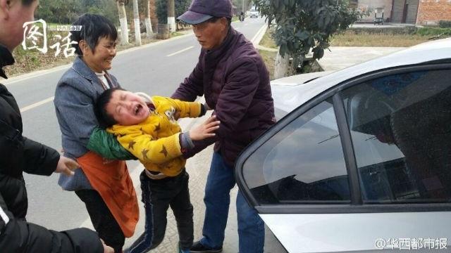 cậu bé 7 tuổi gào khóc và nhất định không cho mẹ đóng cửa xe ô tô để lên thành phố, trong khi ông bà cố gắng kéo em lại phía sau