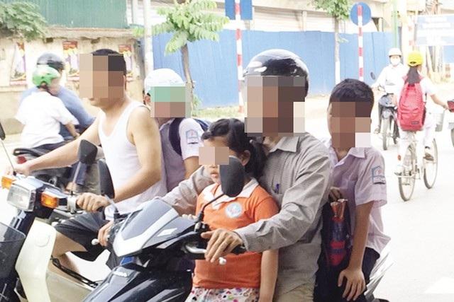 Phụ huynh vô tư kẹp 3 trước cổng trường tại Hà Nội trong khi con em không đội mũ bảo hiểm. (Ảnh: Hạnh Nguyên)