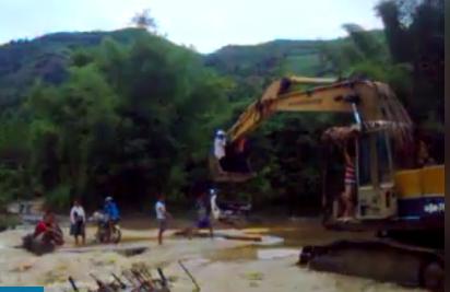 Giáo viên bám vào gầu máy xúc để qua suối (ảnh từ clip)