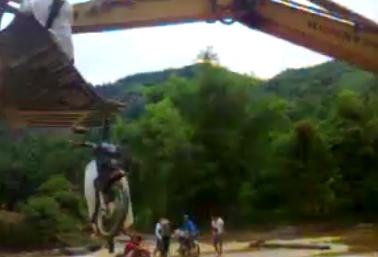 Không những người mà xe máy cũng được móc vào gầu máy để vượt lũ cùng (ảnh từ clip)