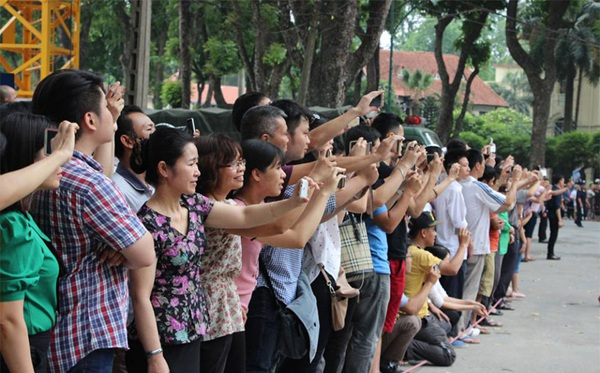 Người dân dùng điện thoại lưu lại khoảnh khắc đoàn xe chở Tổng thống Mỹ lăn bánh trên đường phố Hà Nội