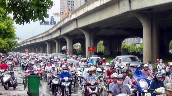 Bị giam dưới trời mưa, người điều khiển xe máy luồn lách tìm cách thoát khỏi tình trạng ùn tắc giao thông trên đường Nguyễn Xiển