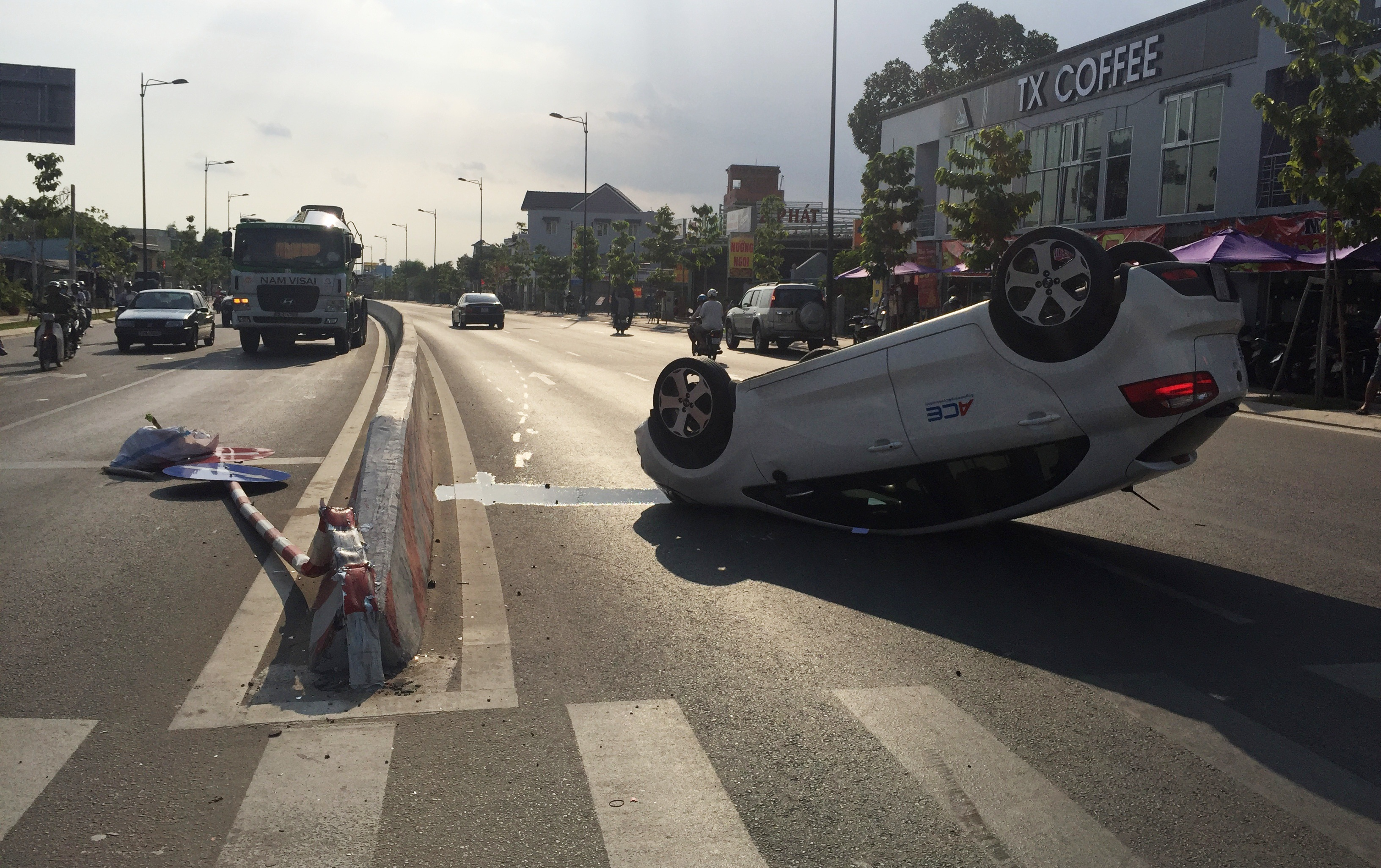 Chiếc du lịch 4 chỗ bất ngờ lao vào dải phân cách, tông gãy biển báo giao thông rồi lật ngữa giữa đường Phạm Văn Đồng.