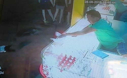 Hình ảnh camera ghi lại việc tên cướp dùng khúc gỗ tấn công nhưng bị chủ tiệm chống trả.
