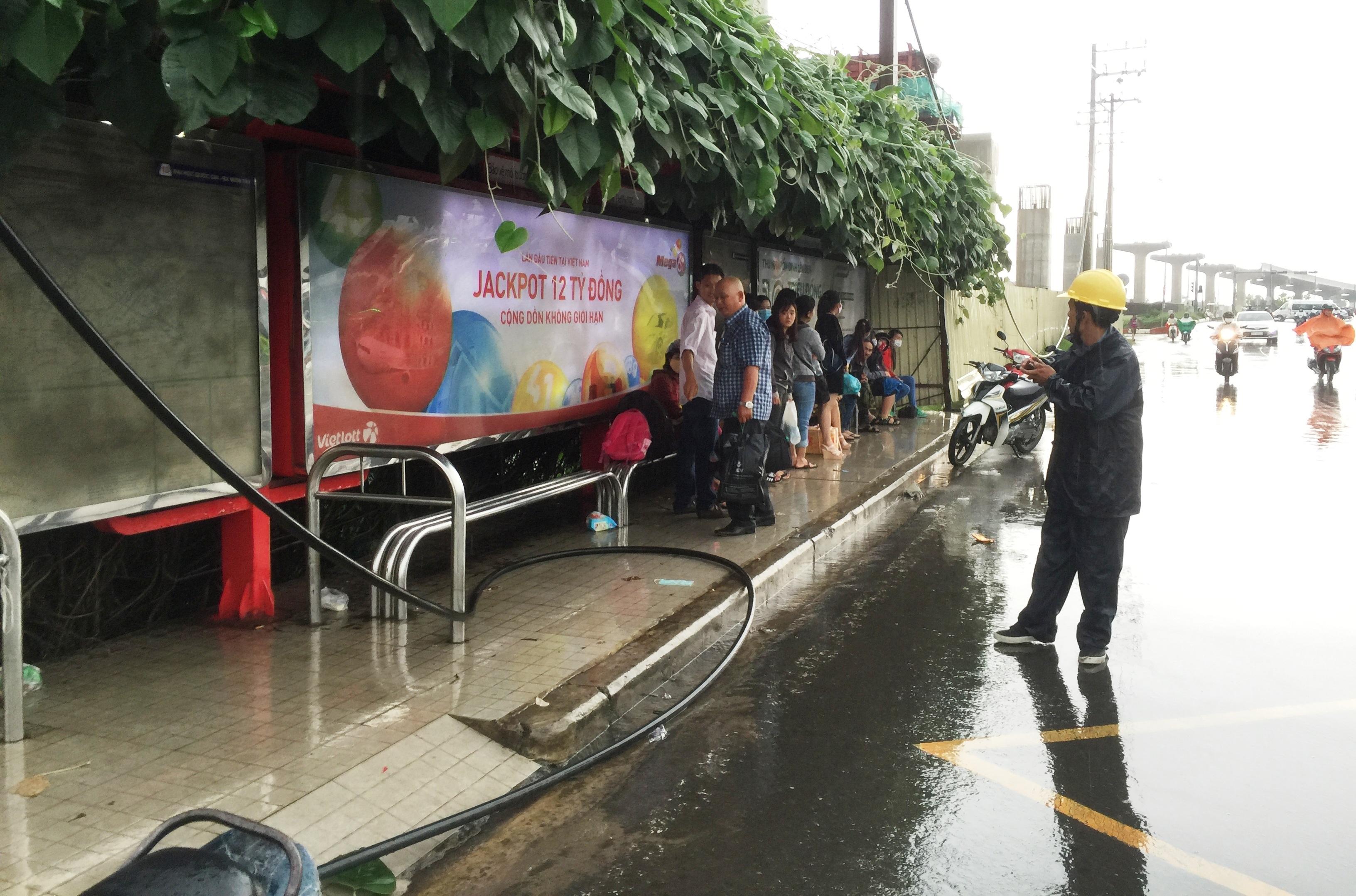 Dây điện đứt ngang, toé lửa rơi xuống đường, ngay sát những người dân đang trú mưa.