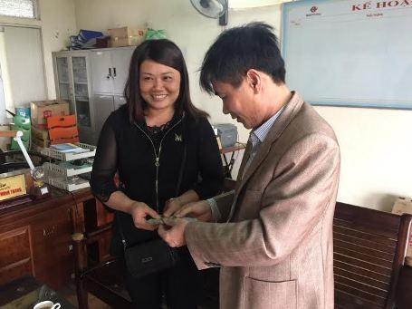 Đại diện Trạm xăng dầu Minh Phương trao lại số tiền 18 triệu đồng cho chị Tuyên