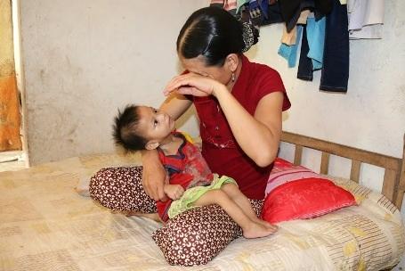 Chị Thu nhìn con quằn quại đau đớn vì bệnh tật mà đành bất lực vì nhà quá nghèo