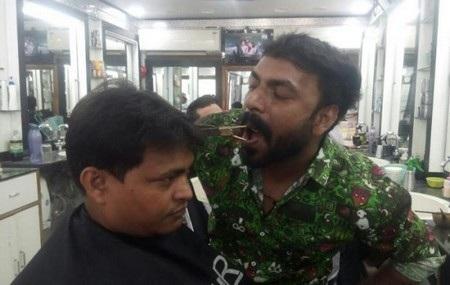 Thay vì dùng tay, Ansar ngậm kéo trong miệng của mình để cắt tóc cho khách hàng