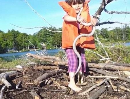 Cô bé thản nhiên dùng tay không bắt lấy con rắn như thể một thứ đồ chơi
