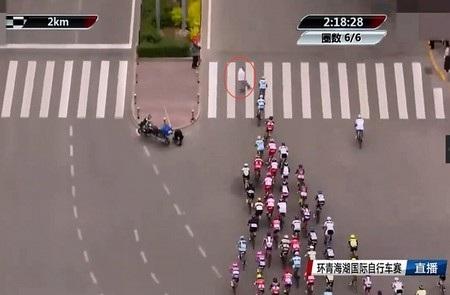 Người đàn ông (khoanh tròn màu đỏ) bất ngờ băng qua đường đúng lúc đoàn vận động viên đua xe đạp đi tới
