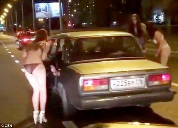 Những cô gái trong trang phục nội y đang chặn xe trên đường để xin tiền