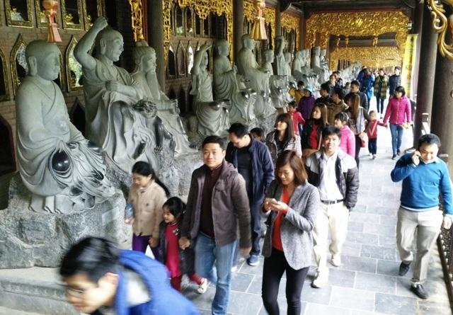 Du khách, phật tử từ khắp mọi miền tổ quốc và nước ngoài đổ về ngôi chùa lớn nhất Việt Nam này để chiêm ngưỡng nhiều kỷ lục Châu Á và Việt Nam. Trong ảnh du khách đang tham quan Hành lang La hán với nhiều kỷ lục tại chùa Bái Đính.