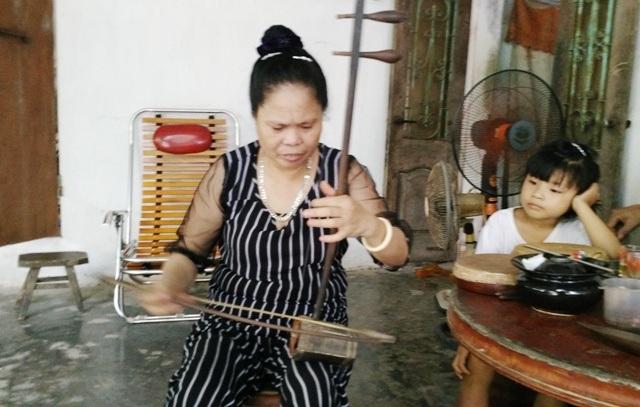 Chị Nguyễn Thị Mận - con gái nghệ nhân Hà Thị Cầu cùng cây nhị khi còn sống thần xẩm thường dùng (ảnh: Thái Bá)