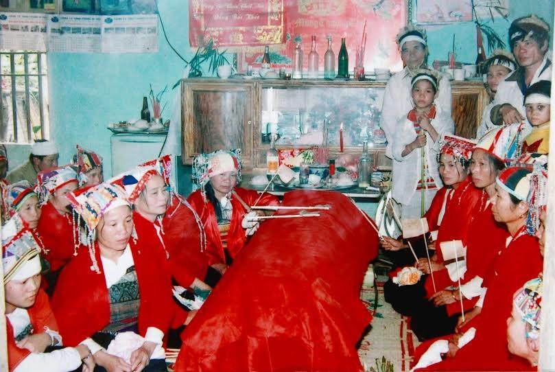 Các nàng dâu mặc trang phục đỏ quạt ma trong một đám tang