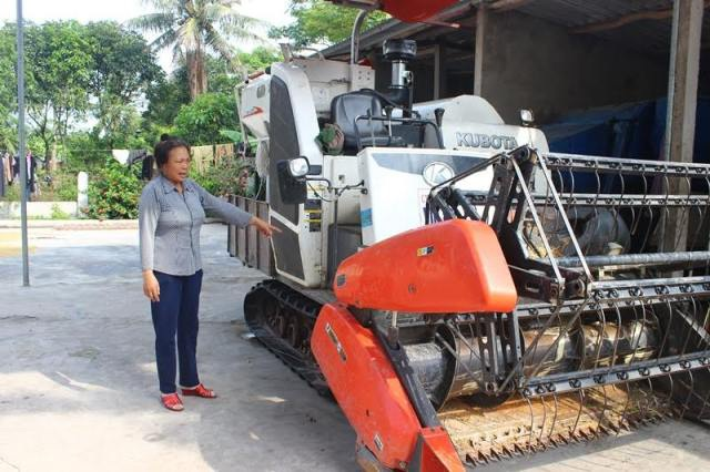Bà Thêm bên chiếc máy gặt đập liên hợp được chính quyền khuyến khích mua để phục vụ bà con nông dân