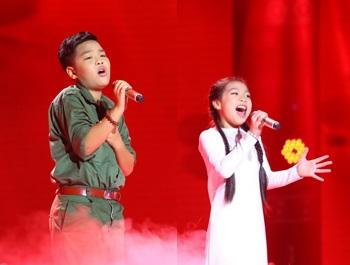 """Hai thí sinh Tiến Quang và Hải Yến biểu diễn ca khúc """"Màu hoa đỏ"""", một ca khúc đầy tính hào hùng, hai thí sinh nhí đã trình diễn thành công như những giọng ca chuyên nghiệp, không thua kém các ca sĩ đã trình diễn. Phần bè phối của hai thí sinh cũng nâng đỡ cho nhau để ca khúc vừa kỹ thuật vừa cảm xúc."""