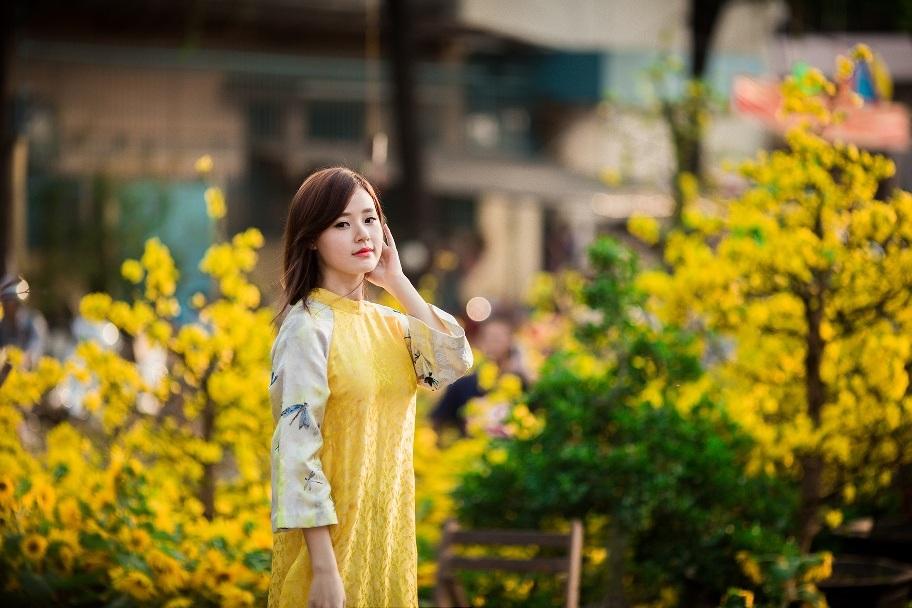 Áo dài màu vàng kết hợp sắc trắng và hoa văn đơn giản nhưng vẫn toát lên sự sang trọng