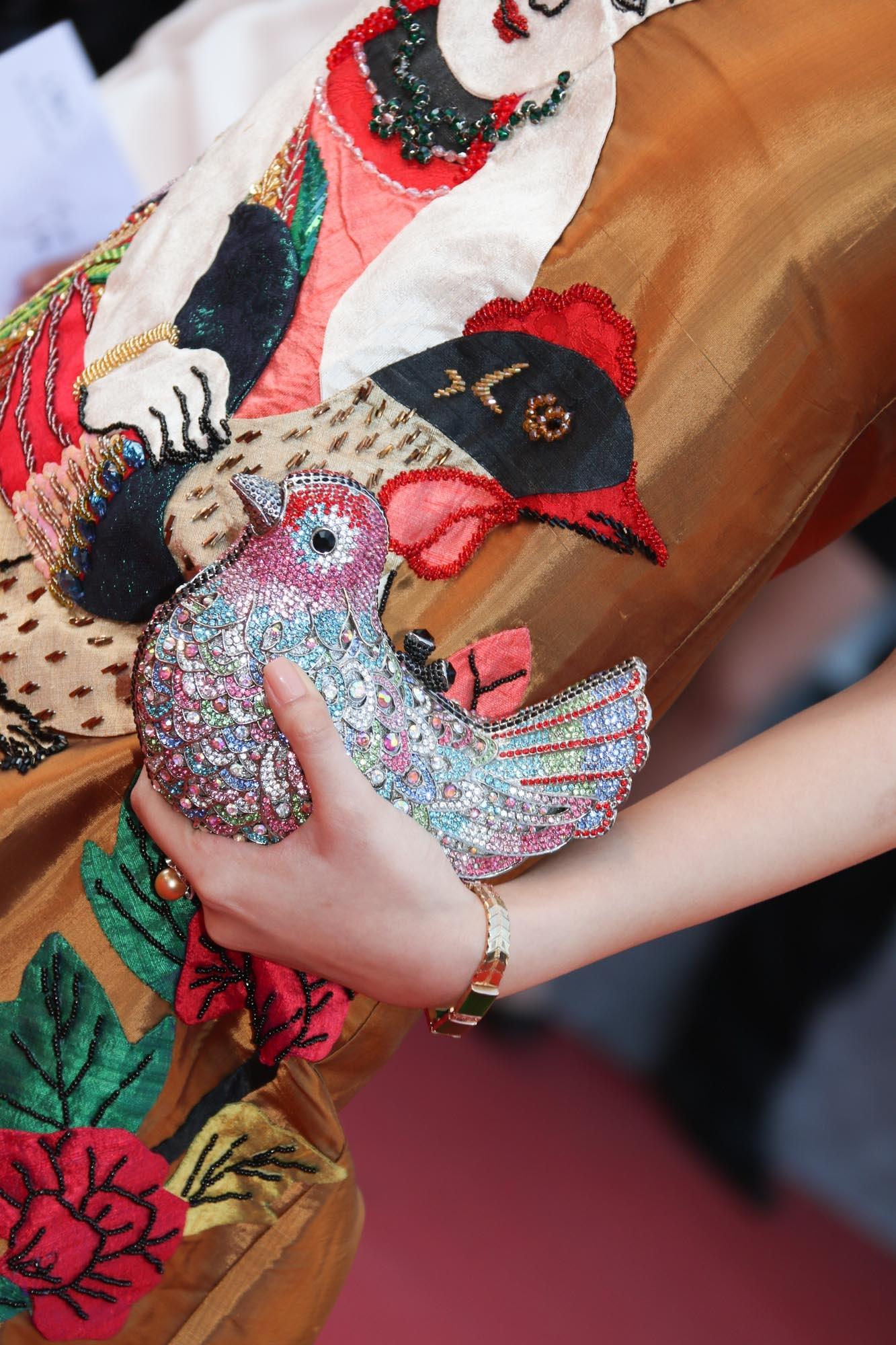 Cô diện một chiếc váy có họa tiết tranh Đông Hồ được thêu tay tỉ mỉ và đẹp khéo léo kết hợp cùng chiếc clutch hình chú chim đính hạt lấp lánh, khăn vấn tóc... tạo nên tổng thể khá hài hòa, thể hiện được nét riêng của một diễn viên Châu Á.
