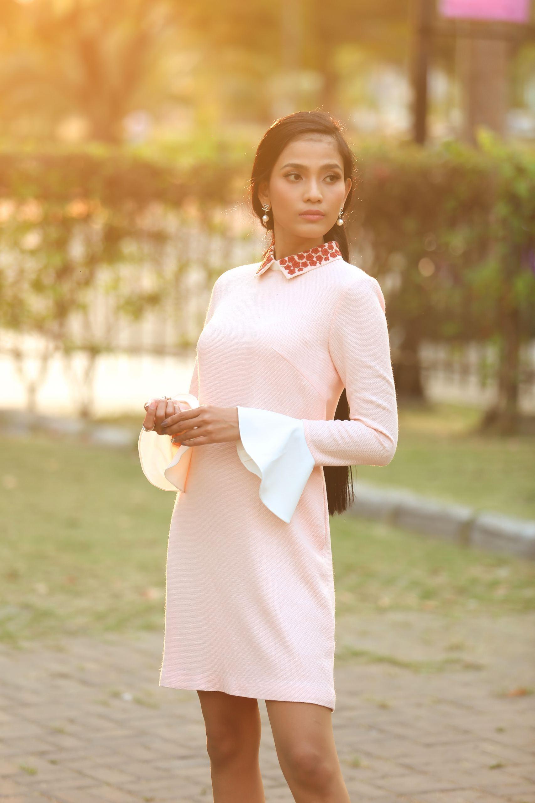 Chiếc đầm suông với một màu trắng tinh khôi tưởng chừng như thật nhàm chán nhưng lại tạo ấn tượng với người đối diện bởi những chi tiết như phần cổ đính hoa tông cam nổi bật, cổ tay nhún bèo.
