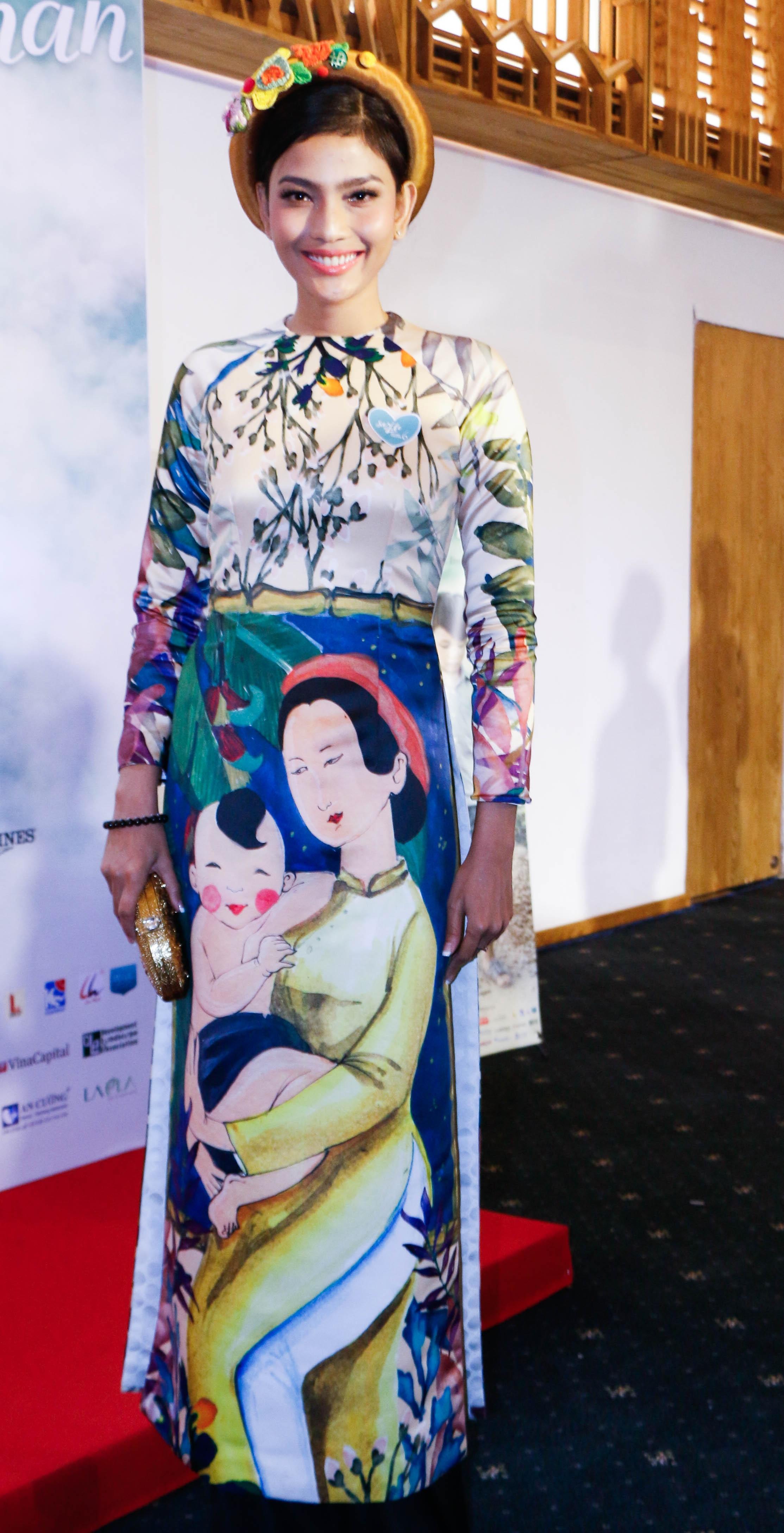 Á hậu Trương Thị May khoác lên mình bộ áo dài với hình ảnh người mẹ ôm đứa con rất tình cảm.