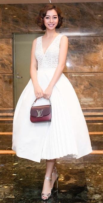 Jennifer Phạm ghi điểm phong cách thời trong tuần này bằng bộ váy trắng, phía trên xẻ ngực chữ V, váy bên dưới phồng kiểu công chúa. Cùng túi xách tay hàng hiệu Louis Vuitton, Jennifer còn tinh tế kết hợp đầm với giày cao gót ánh bạc.