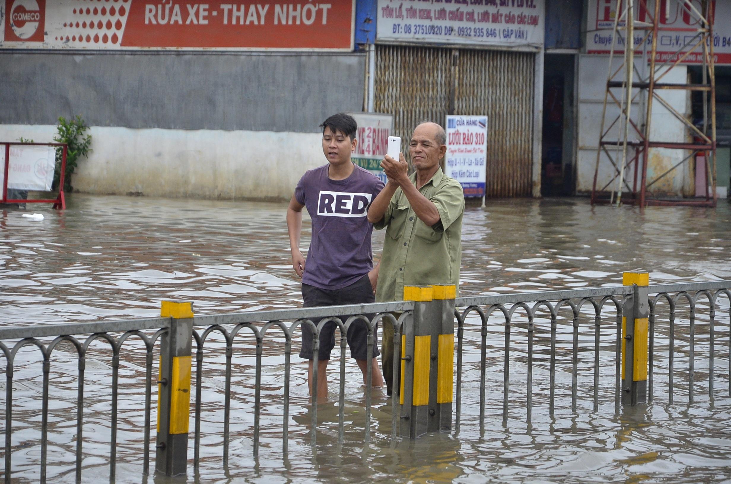 Một người dân đứng chụp hình giữa đường ngập