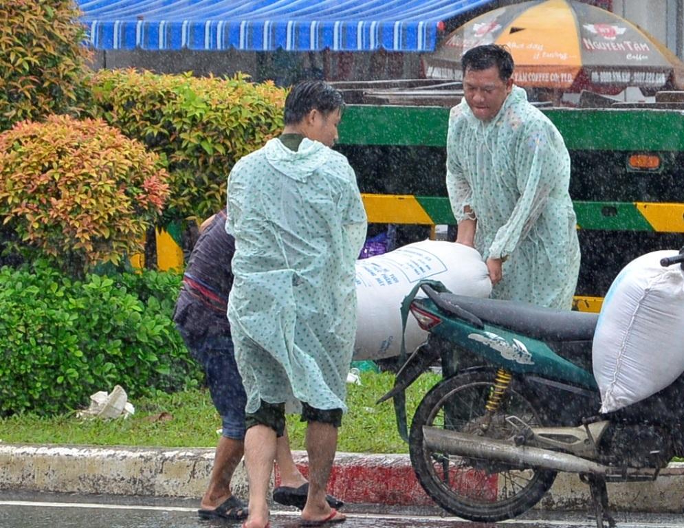 Hai cán bộ công an phường mặc áo mưa ra đẩy xe, bê hàng hóa giúp dân.