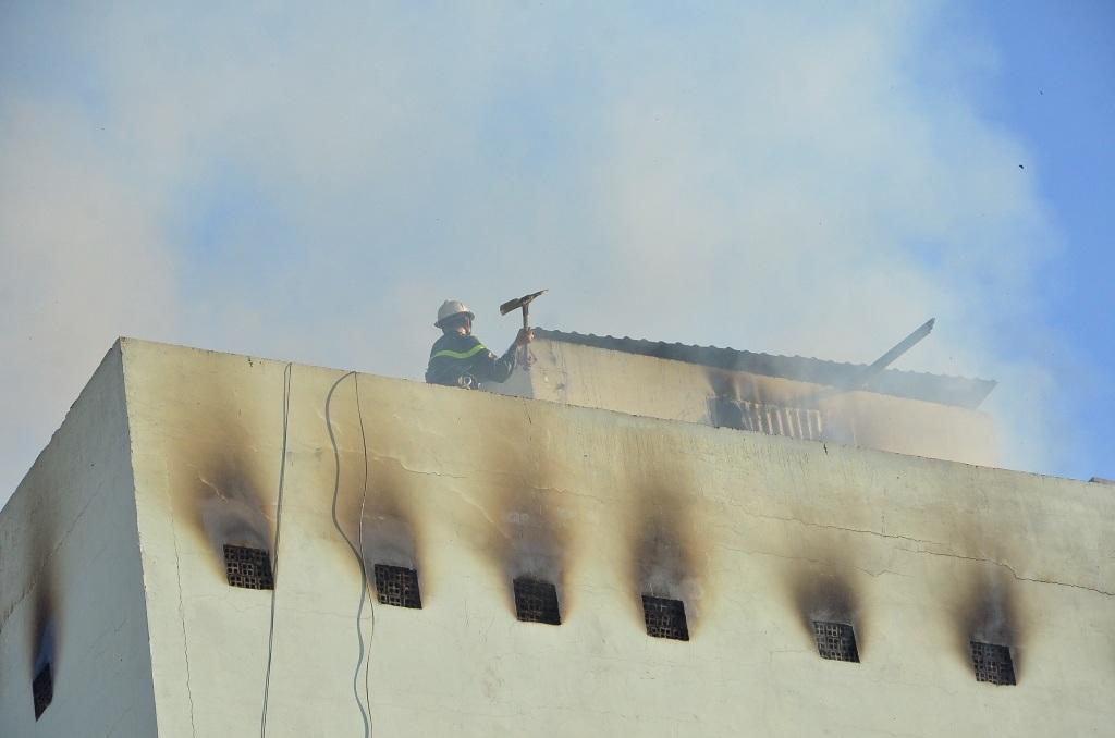 Lính cứu hỏa phá tường trên nóc tòa nhà để cho khói thoát ra ngoài.