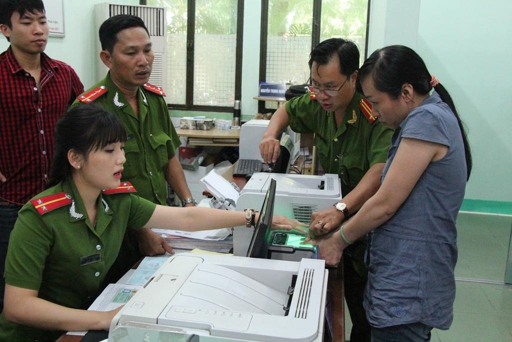 Cán bộ Đội chứng minh nhân dân hướng dẫn người dân lấy dấu vân tay bằng máy.