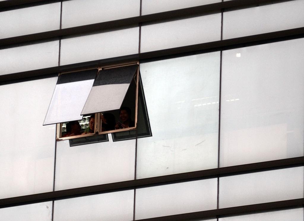 Nhiều người dân làm việc ở các tòa nhà dọc đường Nam Kỳ Khởi Nghĩa hé cửa sổ để nhìn đoàn xe của Tổng thống Obama đi qua
