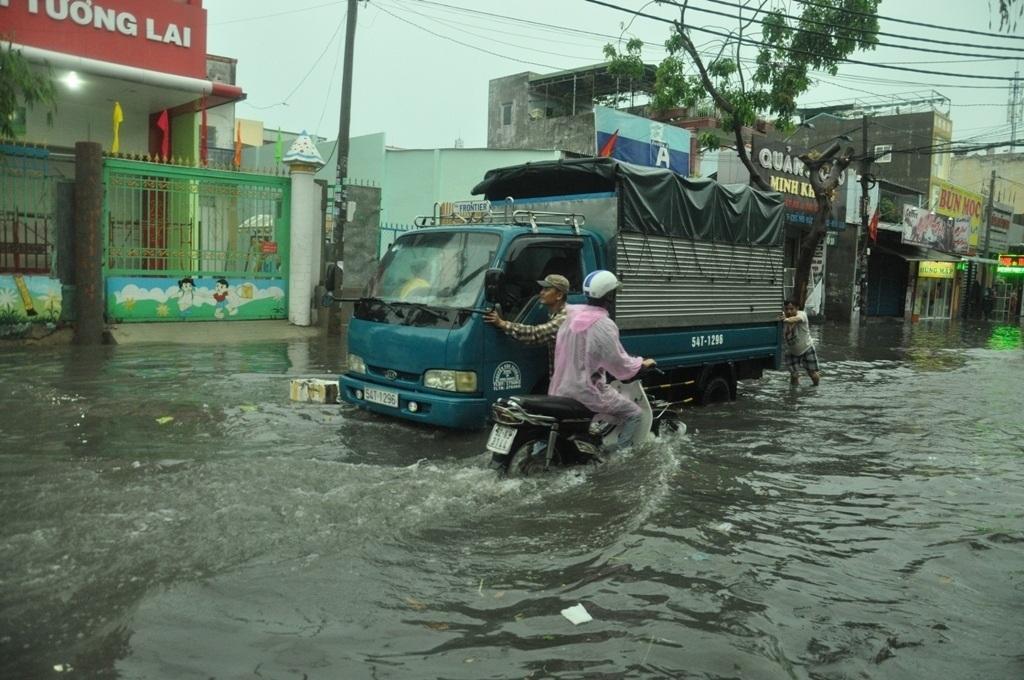 Lái và phụ xe hợp sức đẩy chiếc xe tải chết máy qua vùng ngập