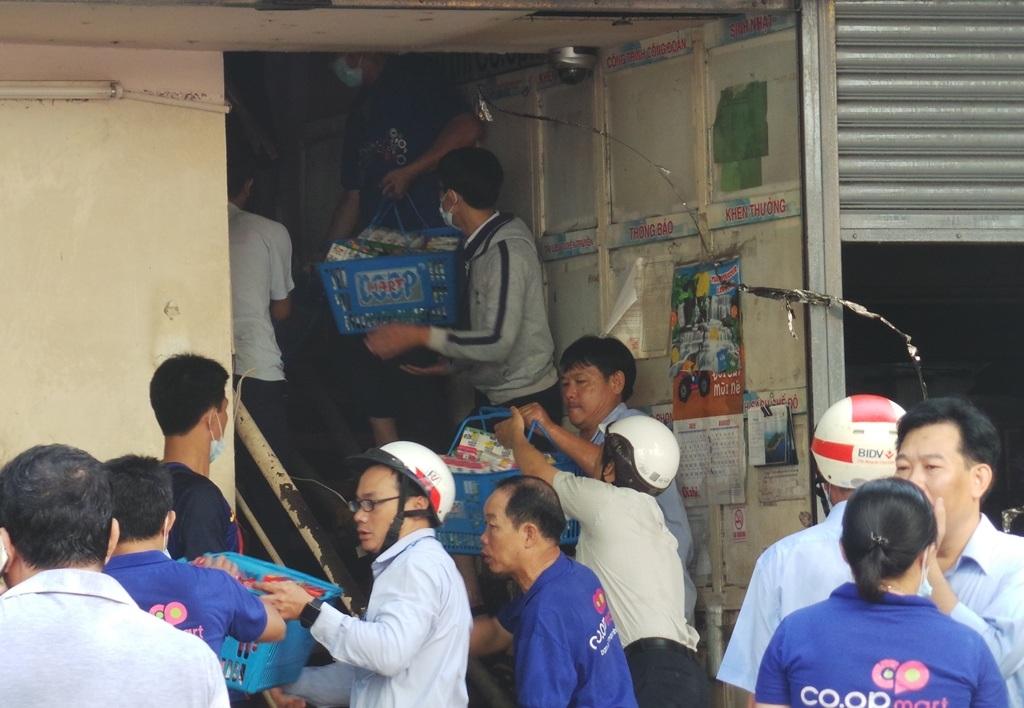 Nhân viên siêu thị di chuyển hàng hóa ra ngoài