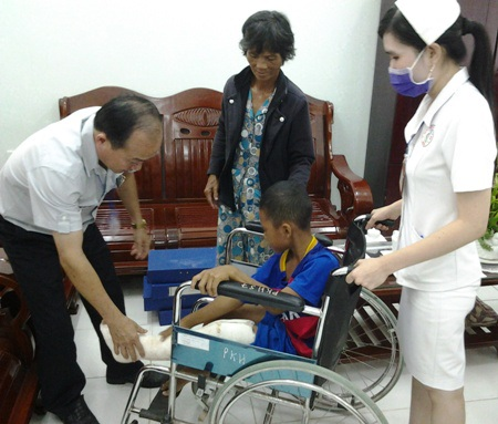 Ông Huỳnh Văn Dũng- Giám đốc Bệnh viện Đa khoa thị xã Giá Rai hỗ trợ cùng gia đình đưa em Phát lên xe lăn về nhà.