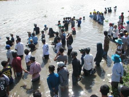 Không còn chỗ đứng trên bờ, nhiều người đổ xuống cả dưới sông để xem.