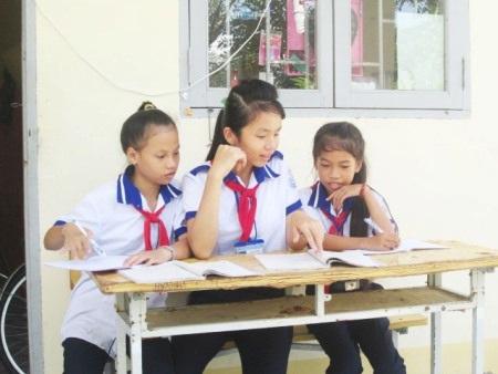 Em Ngân (giữa) luôn vui vẻ và hướng dẫn nhiệt tình đối với các bạn cùng lớp và lớp dưới bị mất kiến thức.