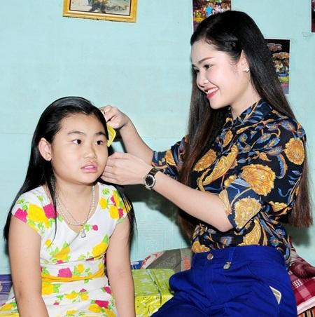 Á khôi Lê Thị Như Quỳnh thân thiện chải tóc cho một em gái nhỏ.
