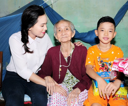 Hoa khôi Nguyễn Thùy Trang ân cần thăm hỏi sức khỏe của một cụ già.