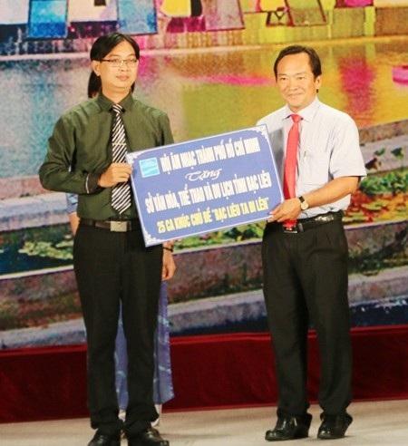 Nhạc sĩ Nguyễn Quang Vinh- Phó Chủ tịch TT Hội Âm nhạc TPHCM (trái) trao tặng bảng tượng trưng 25 ca khúc viết về Bạc Liêu cho đại diện lãnh đạo Sở VH-TT&DL tỉnh Bạc Liêu.