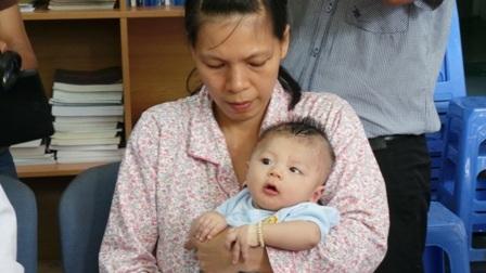 Bé Phát trong vòng tay lo lắng của mẹ khi đến bệnh viện tái khám