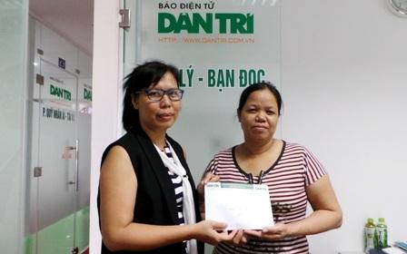 Nhà báo Lý Toàn Thắng (bên trái) trao tiền bạn đọc giúp đỡ gia đình chị Thuyến