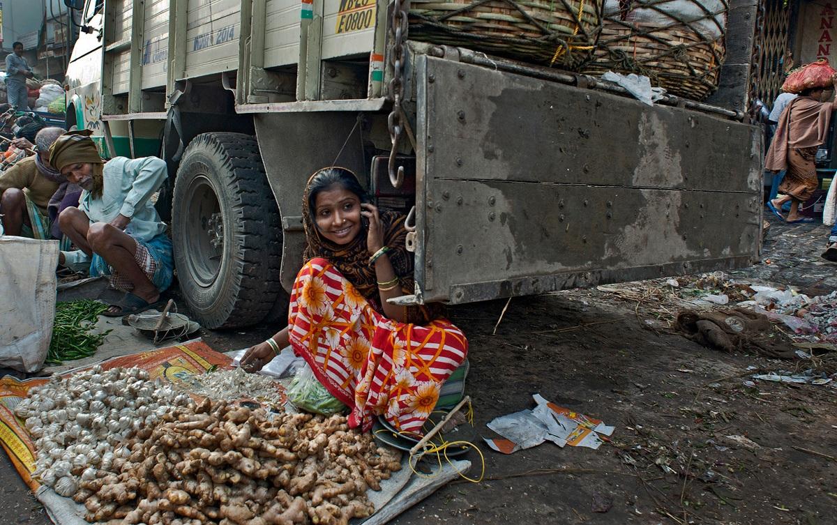 Đến từ ngôi làng cách xa tới 50 km, cô gái người Ấn Độ ngồi bán gừng và tỏi trong thành phố. Cũng như nhiều người lao động khác, cô không có quầy hàng cố định để bày bán. Tác giả: Subrata Adkhikary