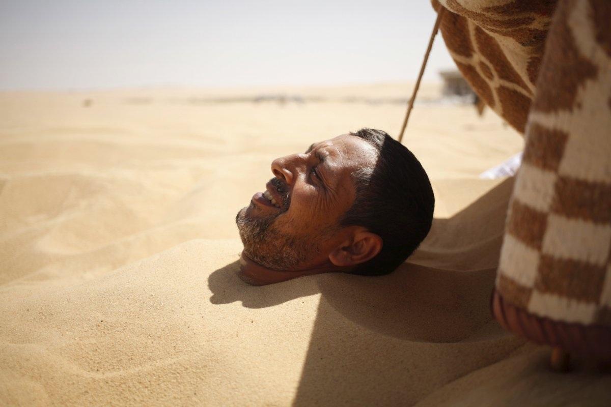 Cát ở sa mạc Siwa, Ai Cập, được người dân dùng như một hình thức trị liệu giúp chữa bệnh thấp khớp, vô sinh. Trong ảnh là hình một người đàn ông đang chôn vùi trong cát để trị bệnh.
