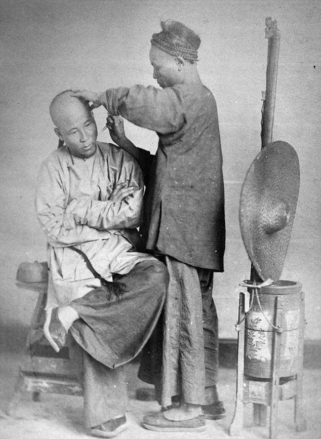 Một người thợ đang chăm chú cắt tóc và cạo đầu cho khách.