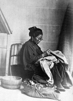 Người phụ nữ đang chăm chú khâu vá.